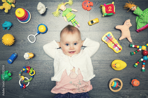 Obraz cute baby girl with lot of toys on the floor. top view - fototapety do salonu