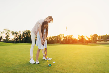 A woman is teaching a girl to play golf. The girl is preparing to hit, the woman is standing behind her and directs her