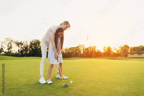 Poster Golf A woman is teaching a girl to play golf. The girl is preparing to hit, the woman is standing behind her and directs her