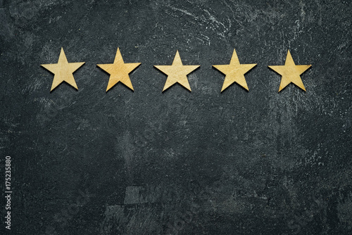 Obraz Five stars in a row on a black rustic cement boards. Conceptual of service rating and quality of trade. Top view, copy space for your text. - fototapety do salonu