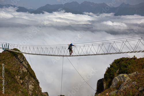 Man walking on suspension bridge and looking at cloudy mountains below.