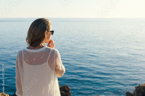 Photo pensive girl looking at the sea sunset