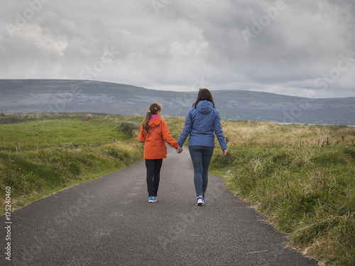 Fényképezés  Mother and daughter walking on a country road holding hands together, The Burren mountains in the background, west coast of Ireland