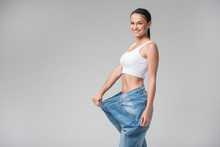 Pretty Young Woman Presenting Result Of Weight Loss