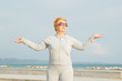 Adult woman on the background of the sea. Senior woman in tracksuit enjoying life. Fitness classes in the open air near the sea and the beach. Lifestyle adult retired.