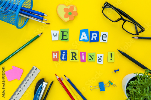 Fotografía  WE ARE HIRING CONCEPT ON yellow work place, office background with supplies