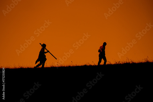 Foto op Canvas Militair Silhouettes of traveler with backpacks hiking top of mountain on sunset at Doi Mon Jong Chiang Mai Thailand.