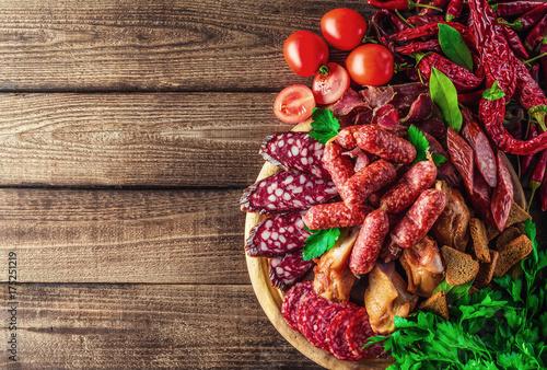 Plakat Tacka na jedzenie z pysznym salami, kawałki plasterki szynki, kiełbasa, pomidory, sałatka i warzywo.