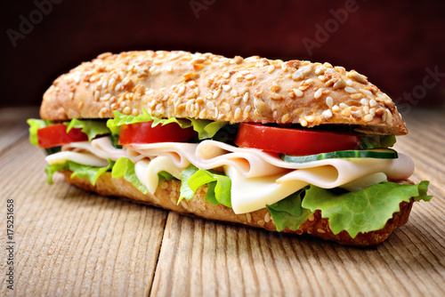 Sandwich with ham, cheese, lettuce, cucumber and tomato. Selective focus