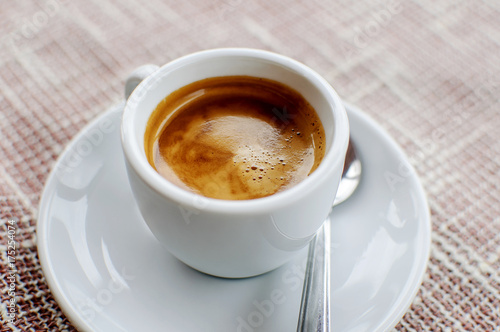 A cup of freshly prepared espresso coffee with foam on fabric, horizontal image Wallpaper Mural