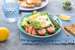 Healthy salad with avocado, corn salad, smoky salmon, eggs and tomatoes for breakfast. Close up