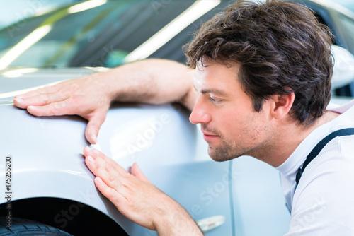 Obraz na plátně Male mechanic examine car finish on dents or scratches in workshop