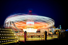 Spinning Ride In A Fair At Night With Colorful Lights