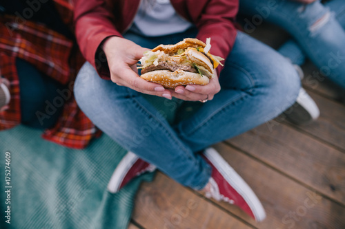 Tasty burger in woman's hands. Takeaway junk food top view. Unhealthy meals and hurry eating, friendship and sharing time together concept