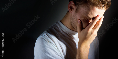 Fotografia man with a hand on his face on a dark background, facespalm