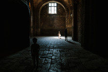 Little Girl Runs Into Light On The Floor Of A Historical Building From A Window High Above Her.