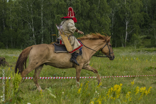 Photo  jockey, a rider on horseback jumps, dressed in an old folk costume of a nomad