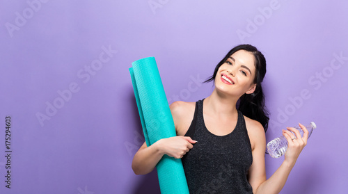 Wall Murals Yoga school Happy young woman holding a yoga mat