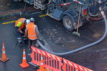 Road Workers Cleaning Sewage In City Street