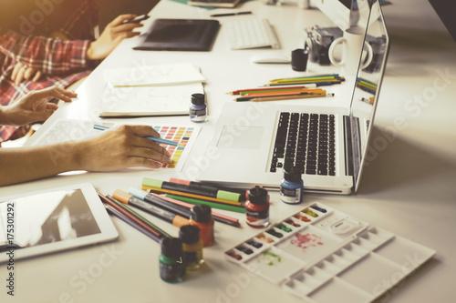 Plakat Młody projektant grafik komputerowych pracuje na nowożytnym komputerze stacjonarnym podczas gdy używać graficzną pastylkę przy biurkiem w biurze.