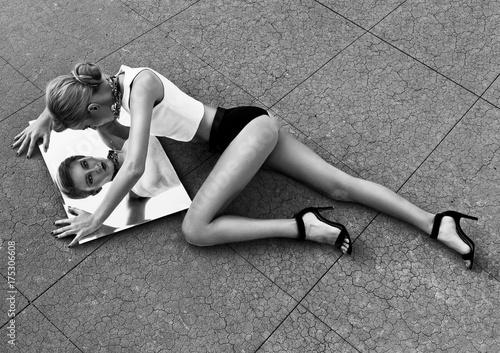 Fototapeta Piękny młody blondynki kobiety lying on the beach na podłoga i patrzeć kamerę myśleć lustro. Ubrana w białą kamizelkę, krótkie czarne szorty i wysokie obcasy. Jej włosy są związane z kucykiem.