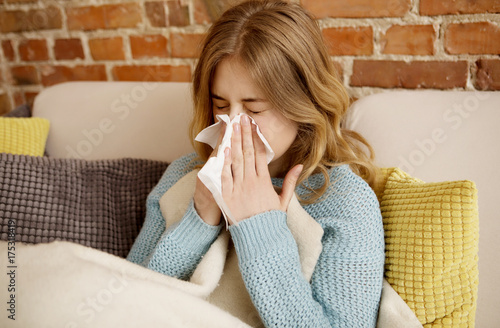 Fotografie, Obraz  Young woman with cold, flu or allergy blowing nose in paper tissue