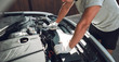 Close-up. A man is fixing a car with a wrench. White car