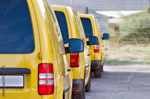 Yellow courier or taxi cars are lined up in the parking lot. Wallpaper Mural