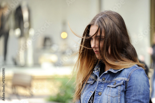 Photo Trendy young hipster woman is looking down sadly with a blowzy hair