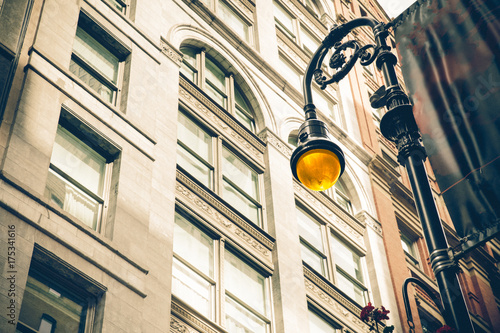Vintage style illuminated streetlamp with New York City apartment buildings in the background Canvas Print