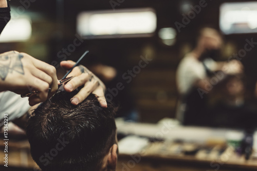 Fotografie, Obraz  Anonymous stylish barber with tattoos cutting hair of male client in chair
