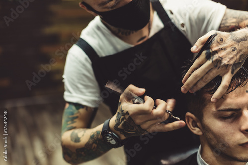 Canvastavla Anonymous stylish barber with tattoos cutting hair of male client in chair