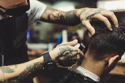Fotografiet Crop tattooed stylist concentrated on shaving man with machine doing hairstyle