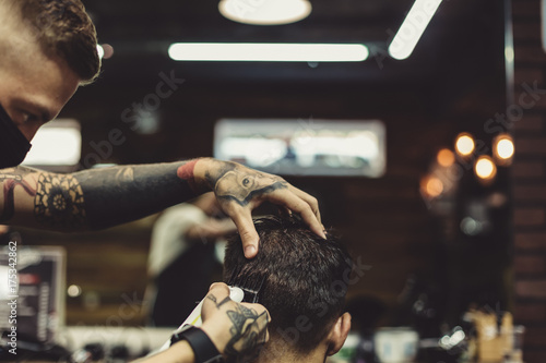 Fotografie, Obraz  Crop tattooed stylist concentrated on shaving man with machine doing hairstyle