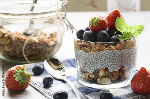 Plakat Jogurt z granola, świeże jagody, nasiona chia i owies w szklance na tle drewna. ścieśniać