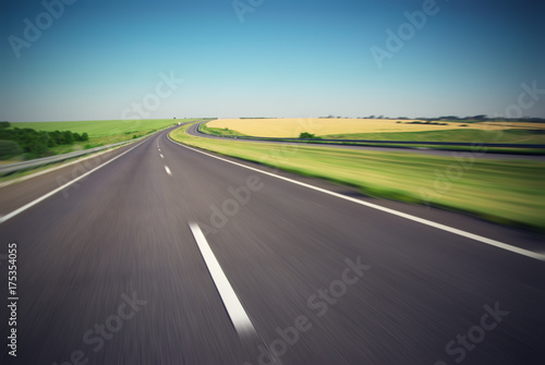 Fotografiet  Motion blurred empty highway with green meadow on horizon