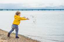 Young Boy Throwing Stones In Sea Water
