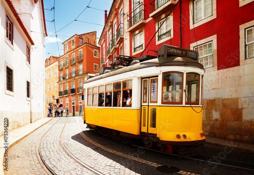 Photo  yellow tram on narrow street of Alfama district, Lisbon, Portugal, retro toned