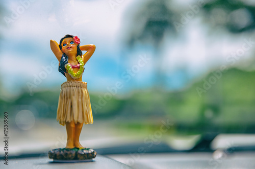 Recess Fitting United States Hula dancer doll on Hawaii car road trip travel vacation. Aloha mini girl doll dancing on the dashboard in tropical nature landscape. Tourism and Hawaiian holiday freedom concept.