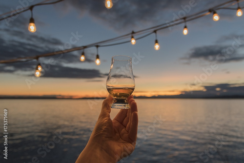 Old fashioned whiskey in hand being held up over the sea at sunset under hanging deck lights.