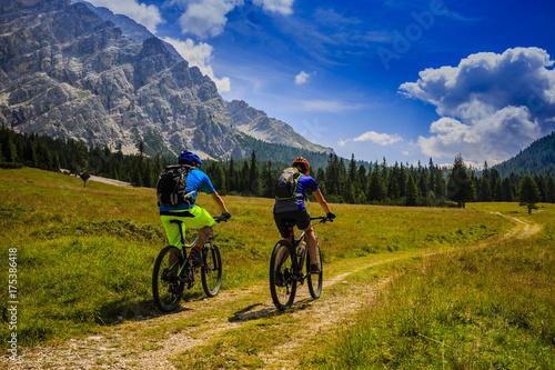 Deurstickers Fietsen Mountain biking couple with bikes on track, Cortina d'Ampezzo, Dolomites, Italy