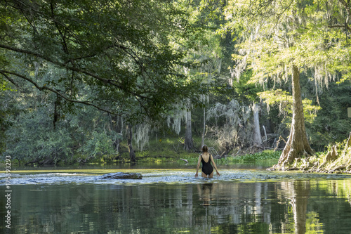 Photo  mature woman wading in shallow clear water at Poe Springs