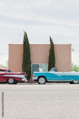 Two vintage cars parked outside a building on the route 66