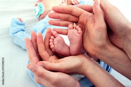 Fototapeta Stopy niemowlęcia otoczone rękami rodziców obraz