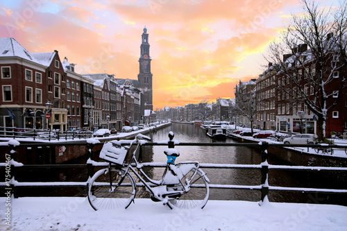 Fotobehang Amsterdam Amsterdam covered with snow with the Westerkerk in winter in the Netherlands at sunset