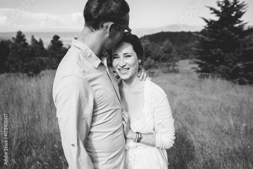 Attractive young couple embracing on a sunny hillside.