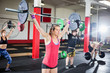 Woman Lifting Barbell With Friends In Fitness Studio