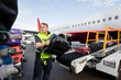 Leinwanddruck Bild - Worker Stacking Bags On Trailer At Runway