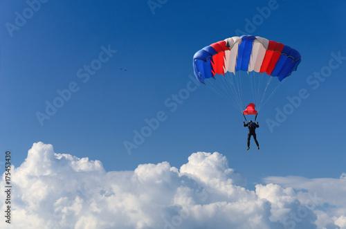 Obraz na plátně  skydiver soars in the sky high above the clouds