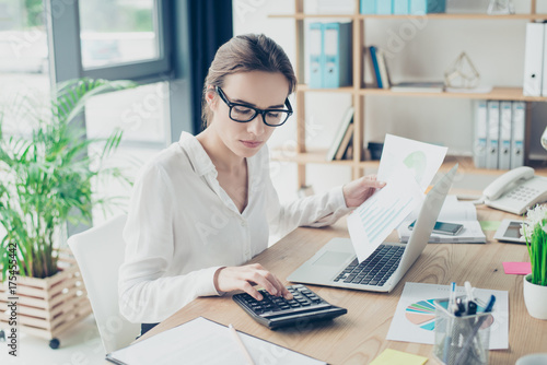 Successful business woman economist in formal wear, sitting at her work place in Tablou Canvas